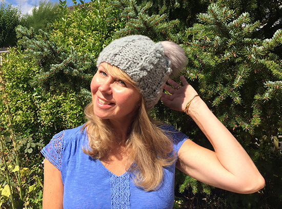 Esther Hartley wearing Cosy Merino Cabled Beanie and synthetic fur bobble