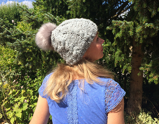Esther Hartley wearing Cosy Merino Cabled Beanie and synthetic fur bobble back view