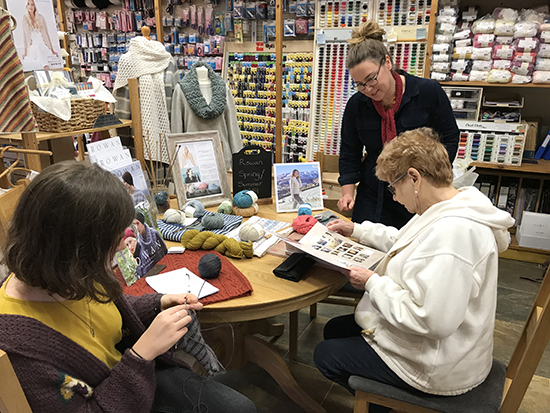 Charlotte (knitting) and Lisa Richardson talking with a customer in Shoreham Knitting & Needlecraft
